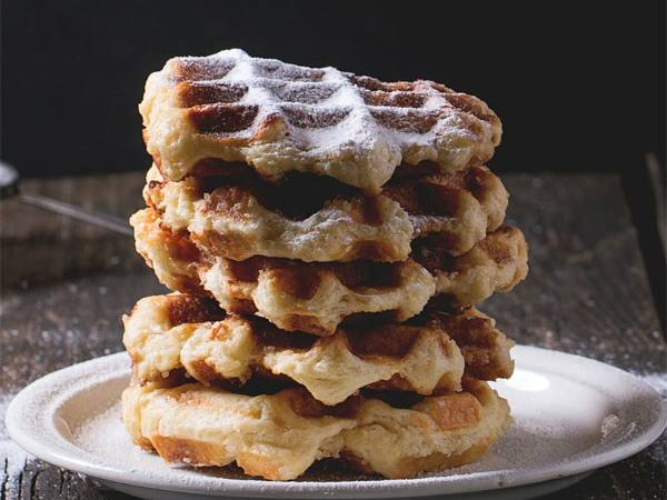 Photo: A stack of belgian waffles dusted with powdered sugar